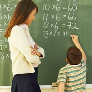 Teacher and a pupil in front of a blackboard. The pupil solves some math exercises