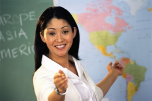 Geography teacher is pointing to a student, asking them a question. She is smiling and wears a white shirt