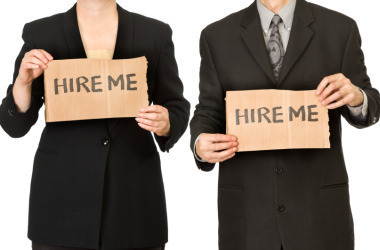 Two job candidates hold small plates of paper, begging the employer to hire them