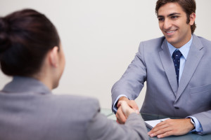 Hand shake at the end of a good job interview, both applicant and interviewer wear gray jackets