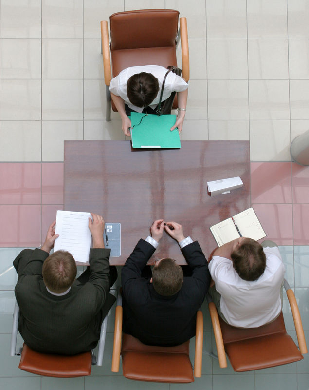 A job candidate sitting in front of an interviewing panel