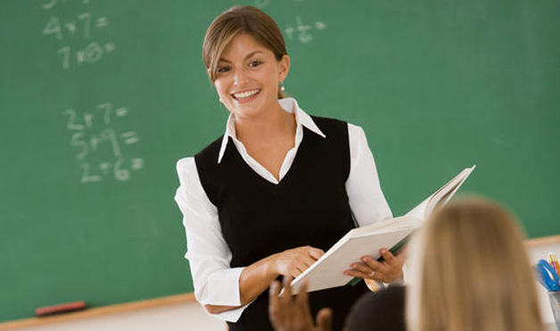 A young female teacher is teeaching mathematics. She is smiling and talking to her pupils in front of a blackboard
